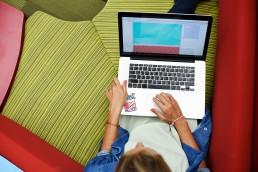 Person sitzt auf Couch mit einem Laptop